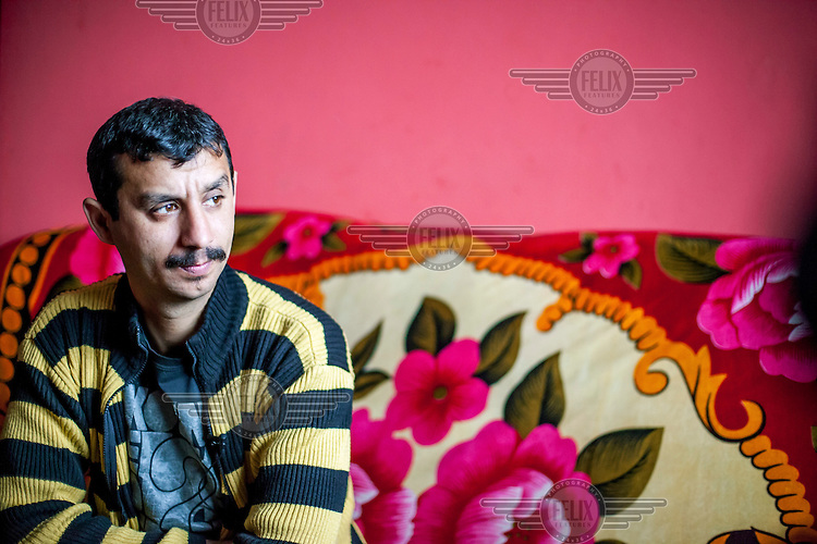 Vojtech Hudac sits on a brightly decorated sofa in his house. His family live in a Roma settlement located on 'Budulovskej Street'.