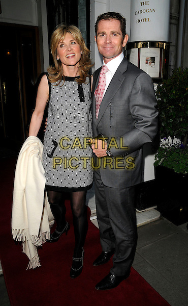 ANTHEA TURNER & GRANT BOVEY .The Cadogan Hotel's 120th anniversary party, 75 Sloane St., London, England..April 15th, 2008.full length black white pattern print dress tights mary janes shoes sleeveless husband wife married grey gray suit carrying white pashmina wrap .CAP/CAN.©Can Nguyen/Capital Pictures.