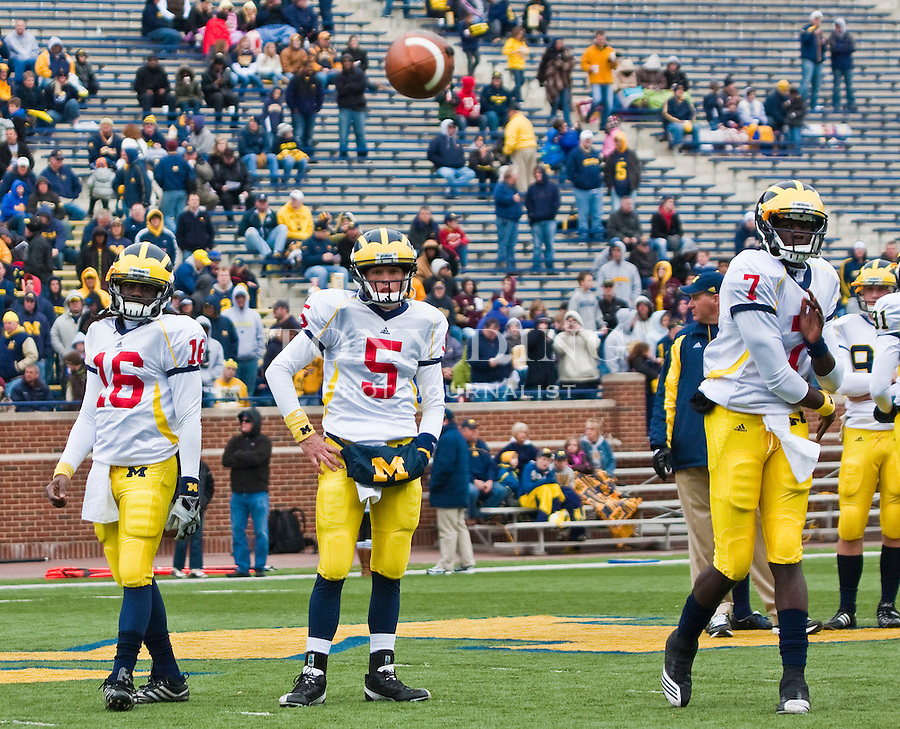 Michigan quarterback Denard Robinson (16) and quarterback Tate Forcier (5) watches quarterback Devin Gardner (7) throw a pass in warmups before the Wolverines' spring football game, Saturday, April 17, 2010, in Ann Arbor, Mich. (AP Photo/Tony Ding)