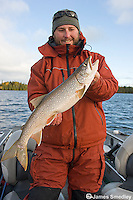 Man holding a summer lake trout in a boat