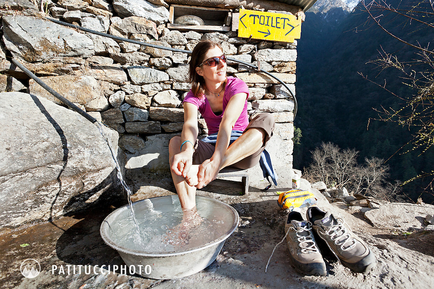 Female trekker sitting outside a guesthouse washing her feet in a tray of water, Langtang Trek, Nepal Himalaya