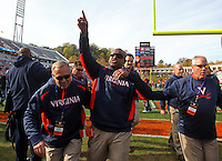 Oct 30, 2010; Charlottesville, VA, USA;   Virginia Cavaliers head coach Mike London, middle, waves to the crowd after the 24-19 upset win over the Miami Hurricanes at Scott Stadium. Mandatory Credit: Andrew Shurtleff
