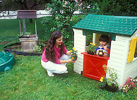Mother and son gardening with playhouse in backyard, watering can, marigolds, lawn