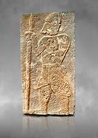 Pictures & images of the North Gate Hittite sculpture stele depicting a God with a spear. 8the century BC.  Karatepe Aslantas Open-Air Museum (Karatepe-Aslantaş Açık Hava Müzesi), Osmaniye Province, Turkey. Against grey art background