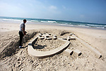 """Palestinian artist Mohammed Totah with amputated leg, works on a sand sculpture reads in Arabic """"my mother"""" to mark the Mother's Day, at the beach of Gaza city on March 21, 2019. Totah, 31 year-old, who had lost his leg during the Israeli war on Gaza Strip in 2008, despite his disability, he succeeded in writing and drawing sculptures by sand on the Gaza beach marking the national events. Photo by Mahmoud Ajjour"""