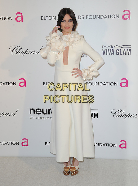 Paz Vega.The 21st Annual Elton John AIDS Foundation Academy Awards Viewing Party held at The City of West Hollywood Park in West Hollywood, California, USA..February 24th, 2013.oscars shoes dress long sleeves white full length gold platform cut out away cleavage corsages cuffs hand on hip arm.CAP/DVS.©DVS/Capital Pictures.