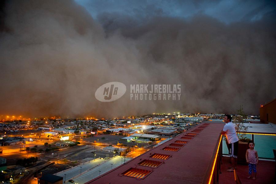 Apr. 26, 2011; Phoenix, AZ, USA; A dust storm converges on downtown Phoenix  haboob sandstorm dust monsoon storm chaser chasing city dusk Arizona father daughter family urban