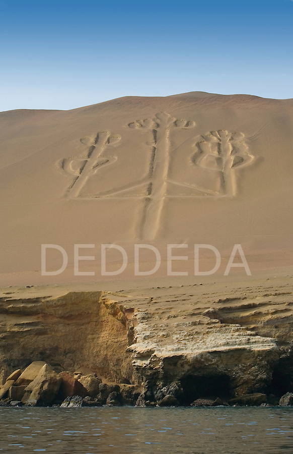 The famous three-pronged Candelabra etched into the coastal hills en route to the Islas Ballestas, located near Paracas and Pisco, Peru. The Candelabra is over 150m high and 50m wide. No one is exactly sure who created the symbol or what is signifies.