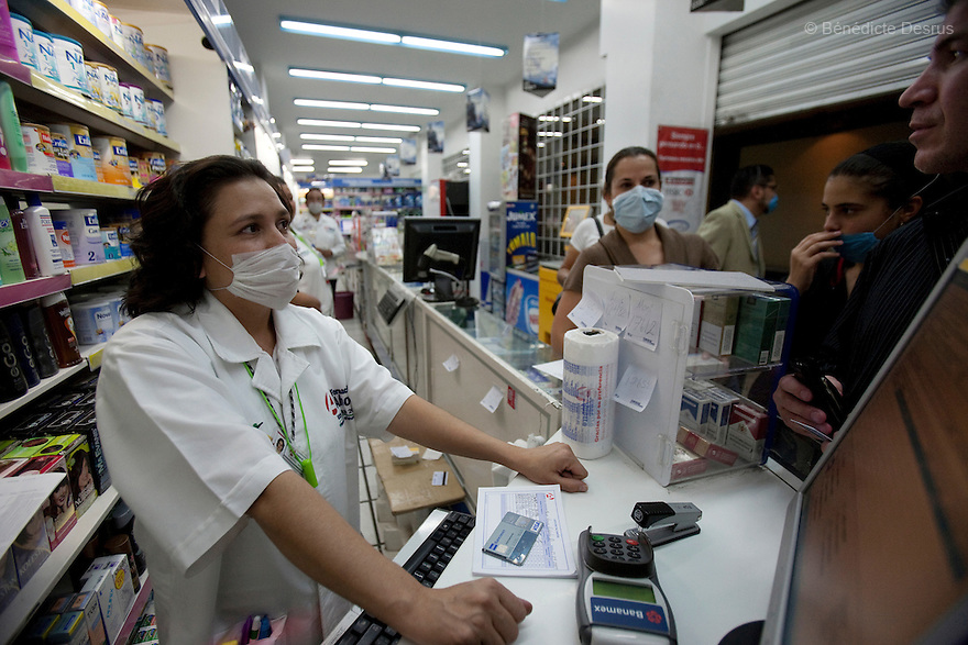 27 April 2009 - Mexico City, Mexico - Employees at a pharmacy purchase supplies ranging from antibiotics, to soap, and vitamins. All surgical masks have run out in the Pharmacies of Mexico City. Residents of the Mexican capital wear surgical masks to protect themselves from the swine Flu. Photo credit: Benedicte Desrus / Sipa Press