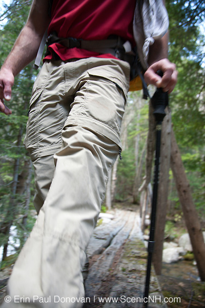 A hiker crossing foot bridge on the Asquam Ridge Trail during the summer months. Located in the White Mountains, New Hampshire USA