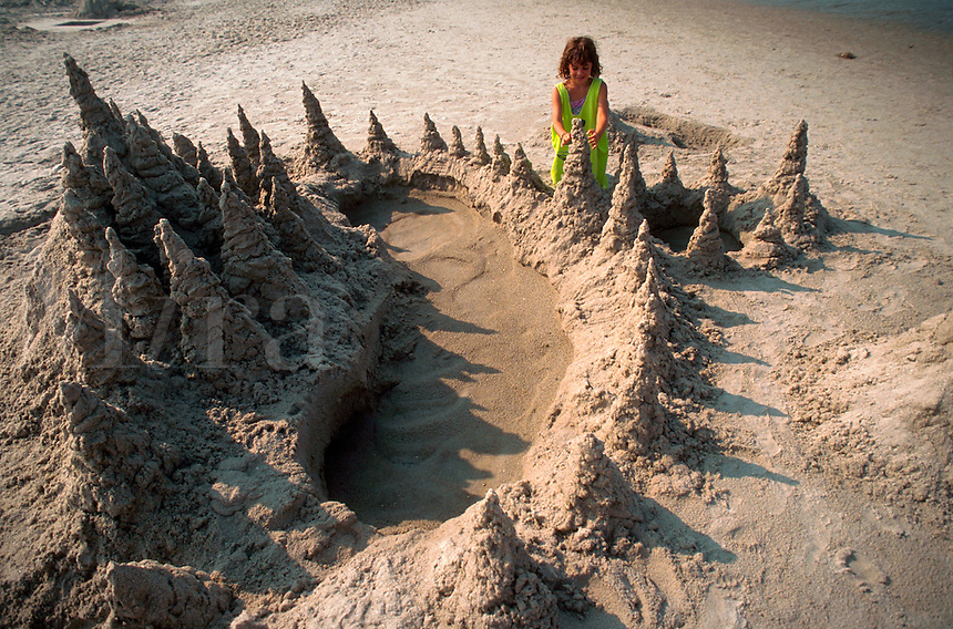 Young girl building an elaborate sandcastle.