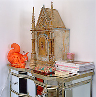 A squirrel light and an elaborately carved wooden box on top of a mirrored glass chest of drawers occupy a corner of this room