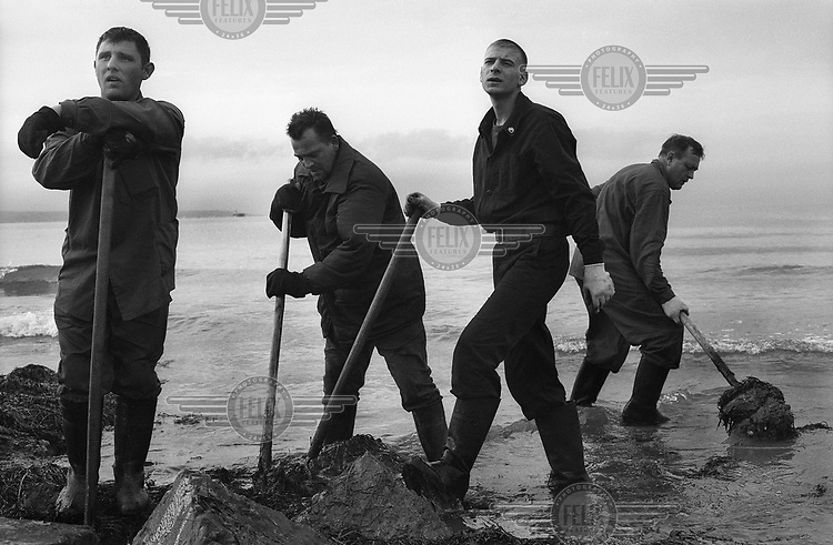 Men clean up oil which has washed up on the coast near Adler on the Black Sea after an oil spill out at sea.