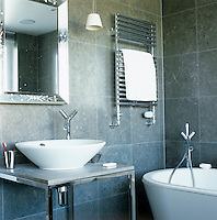 The bathroom is furnished with Philippe Starck's bathroom range and tiled in grey slate