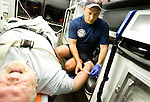 Paramedic Todd Crawley of the Madison, Wis. Fire Department?s Station One shift B tapes a new IV line into a patient?s arm on the way to St. Mary?s hospital on Thursday, July 19, 2007 in Madison Wis.