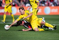 Chris Pontius (13) of D.C. United tumbles to the crowd in the box with Eddie Gaven (12) of the Columbus Crew during the game at RFK Stadium in Washington, DC.  Columbus Crew defeated D.C. United, 2-1.
