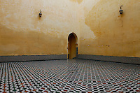 Mausoleum of Moulay Ismail, Meknes, Morocco, 1703, built by Ahmed Eddahbi, pictured on December 21, 2009. An archway in typical Islamic design, pierces a stuccoed wall in the corner of a large room.  Through it stretches a tiled ceramic floor in geometric design, contrasting with the soft apricot walls. The tiled pattern, seen at a low angle, creates a dizzying illusion. Meknes, one of Morocco's Imperial cities, was redeveloped under Sultan Ismail Moulay (1634-1727). It is a fortified city built from pise, or clay and straw, and was designed to be the political capital of Morocco, as opposed to Fez, the religious capital. Picture by Manuel Cohen