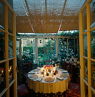 In the evening this lily-filled conservatory transforms into a dining room large enough to seat eight