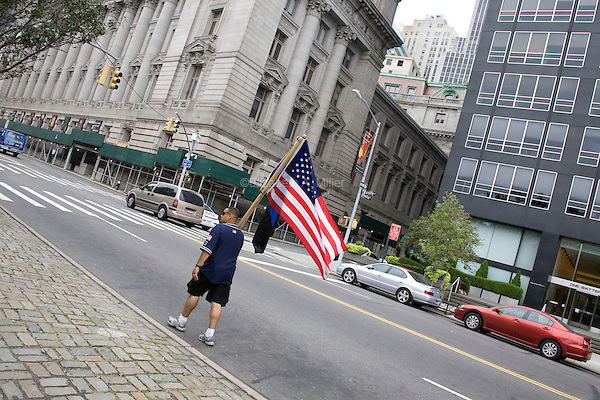 A man walks down the street with an American flag near Battery Park in New York City, New York on the 10th anniversary of the September 11th attacks on 11 September 2011.