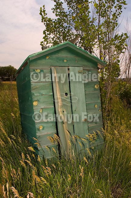 Leaning wooden green outhouse southwest Colorado