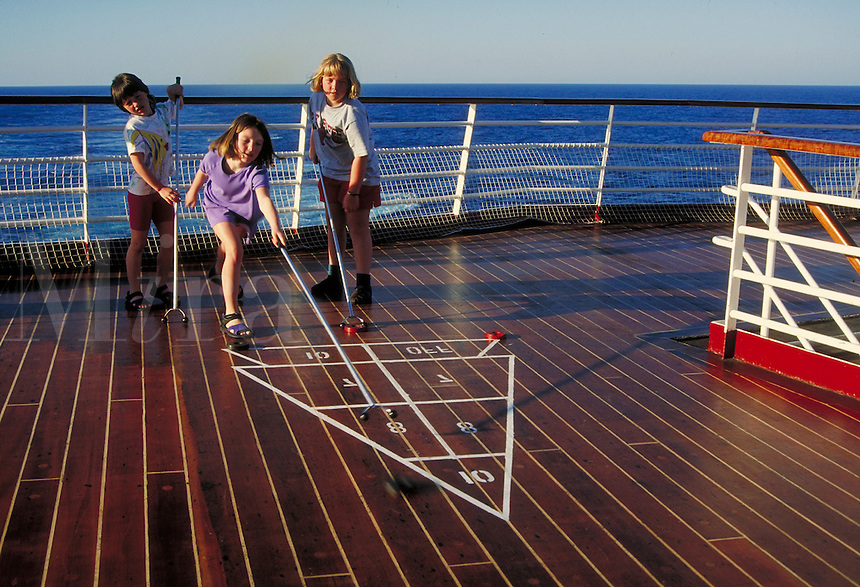"children playing shuffleboard on the deck on ""Song of America"" cruise ship. children."