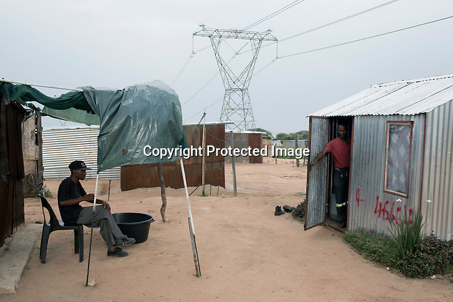 Residents relax in Maropong township outside Lephalale, South Africa. Many people have moved in from rural areas and Zimbabwe to find work at the new Medupi coal power plant. The plant, operated by the state company Eskom will be the fourth largest in the world and is expected to produce electricity in early 2015. Many people live in bad conditions in Maropong, trying to make a living and compete about the few jobs available.