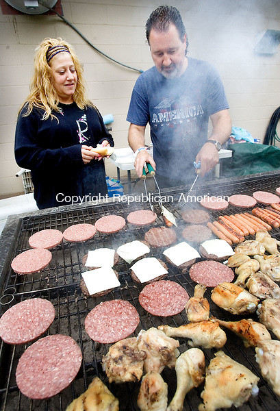 PROSPECT CT. 28 June 2015-062815SV03-From left, Corinne DeSantis of Waterbury waits for her hotdog to finish while Andy Vaichus of Watertown cooks during the annual Lithuanian picnic in Prospect Sunday. The Lithuanian Club of Waterbury Inc. hosted its 11th annual clambake and picnic.<br /> Steven Valenti Republican-American