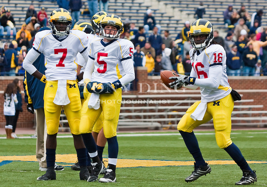 Michigan quarterback Devin Gardner (7) and quarterback Tate Forcier (5) watch quarterback Denard Robinson (16) run through a throwing drill before the Wolverines' spring football game, Saturday, April 17, 2010, in Ann Arbor, Mich. (AP Photo/Tony Ding)