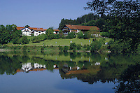 Reflections of properties on Forggensee lake close to Neuschwansein castle. Bavaria, South Germany.