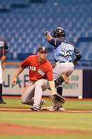 Boston Red Sox first baseman Sam Travis (12) waits for a throw as Cristian Toribio (70) runs through the bag during an Instructional League game against the Tampa Bay Rays on September 25, 2014 at Tropicana Field in St. Petersburg, Florida.  (Mike Janes/Four Seam Images)