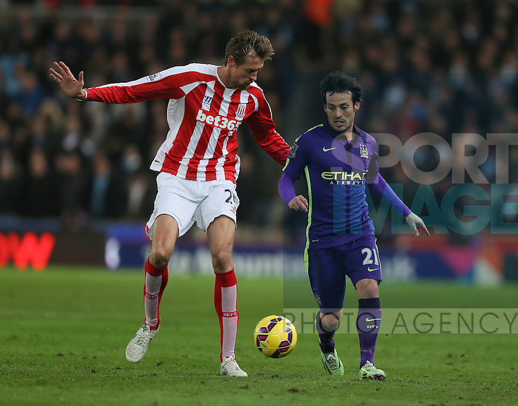 Peter Crouch of Stoke City tussles with David Silva of Manchester City - Barclays Premier League - Stoke City vs Manchester City - Britannia Stadium - Stoke on Trent - England - 11th February 2015 - Picture Simon Bellis/Sportimage