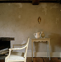 Two jugs sit on a simple wooden table against a mottled plaster wall in the sitting room