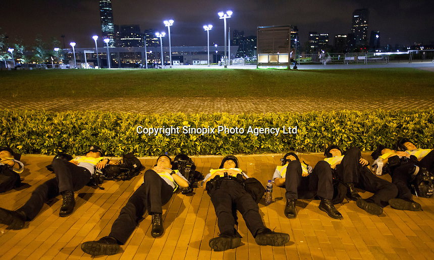 Policemen take a rest at the end of the first day of Occupy Hong Kong, Hong Kong, China, 29 September 2014. Several areas of the city including Central, Admiralty, Causeway Bay, as well as Mong Kok in Kowloon, were locked down by Occupy Central civil disobedience teams who fanned out across the city blocking major thoroughfares as well as side streets, with rip ties, metal barriers, police road cones and any other street furniture available to hand.