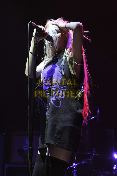 Taylor Momsen.The Pretty Reckless live in concert at Hammersmith Apollo, London, England. 4th November 2011.stage concert gig performance performing music on half length black t-shirt stockings purple print singing side profile hand arm.CAP/MAR.© Martin Harris/Capital Pictures.