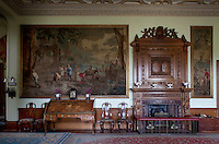 An appropriately elaborate Victorian fireplace, flanked by de Coigny tapestries framed on the walls of the inner hall