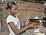Srey Mao, 14, starts a fire and cooks a meal in Khnach, a village in the Kampot region of Cambodia. Along with another sister, she lives with and takes care of her aging grandmother. Her parents died of AIDS.