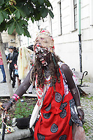 Female participant from prague zombie walk may 2014, having a cane in her left hand,wearing a red,black and white skirt and lots of bracelets and a mask in her forehead