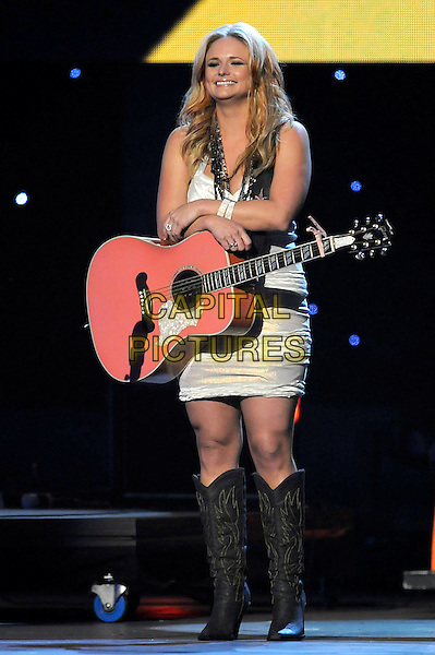 MIRANDA LAMBERT .performs during the 43rd Annual CMA Awards, Country Music's Biggest Night, held at the Sommet Center, Nashville, Tennessee, USA, 11th November 2009. live show on stage  full length concert gig music smiling guitar cowboy boots silver white dress knee high .CAP/ADM/LF.©Laura Farr/AdMedia/Capital Pictures.