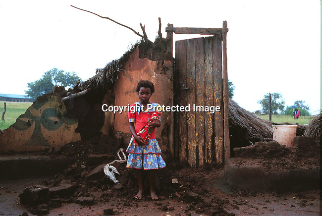 Young girl stands in front of the remains of her house, after flood damage in the Northern Province. 27 February 2000..© Per-Anders Petterssen / iAfrika Photos
