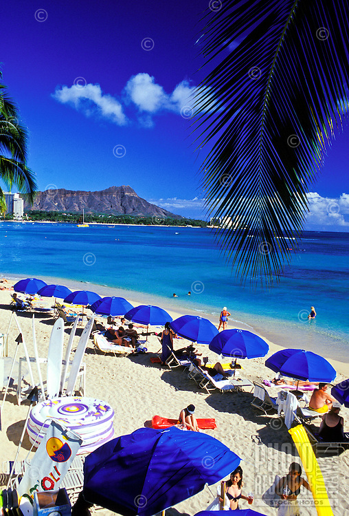 Vacationers enjoy a view of Diamond Head Crater as they relax on the warm, inviting sands of Waikiki Beach. This photo taken from the Outrigger Reef on the Beach Hotel.