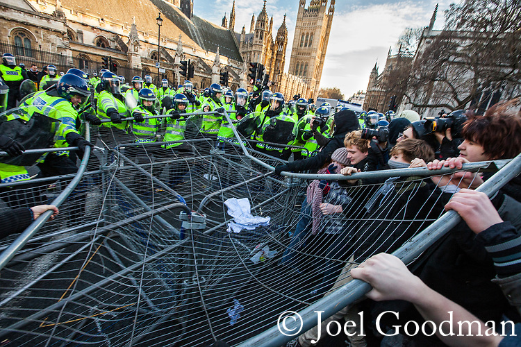 © Joel Goodman - 07973 332324 . 09/12/2010 . London , UK . Students and their supporters tear down barriers erected around Parliament Square as they clash with police during a demonstration in Parliament Square in London against government cuts to student support , Educational Maintenance Allowance ( EMA ) and rising university tuition fees . Photo credit : Joel Goodman