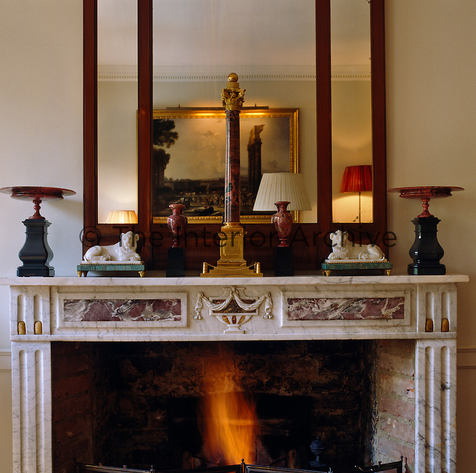A miniature column stands on this marble fireplace flanked by carved alabaster lions and miniature urns