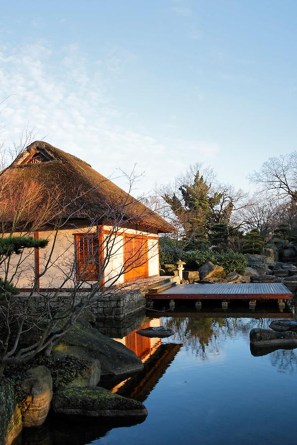 Tea house beside pond in Japanese Garden designed by landscape architect Joshikuni Araki in Hamburg's Planten un Blomen park, Germany