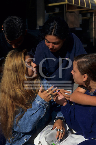 Curitiba, Parana State, Brazil. Three teenagers talking; one with blue long nails.