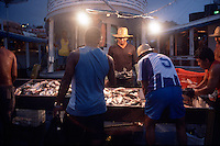 Amazon river fishermen sell their wares at the Panair docks in Manaus, Brazil, Saturday, Jan. 7, 2006. Fishmongers from the city's public markets arrive in the wee hours of the morning to buy their stocks for the day directly from the boats. The Amazon river system boasts more different species of fish than the Atlantic Ocean, but as population increases, so does the pressure on fish stocks in the vast river. (Kevin Moloney for the New York Times)