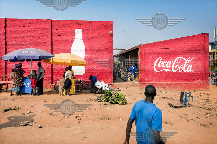 Stall selling mobile phone credits set up infront of building walls covered in a Coca-Cola advertisement.