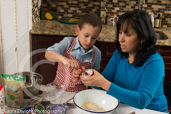 3 year old boy in kitchen at home with mother learning to cook baking, using measuring spoon to add baking powder