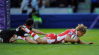 Billy Twelvetrees of Gloucester Rugby scores a try between the posts despite the efforts of Sam Hidalgo-Clyne of Edinburgh Rugby