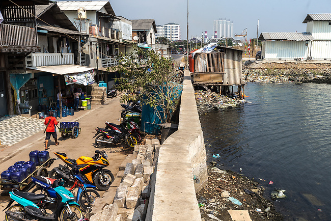 13 August 2019, Jakarta, Indonesia: A local man loads up water barrels for delivery on the streets of Muara Baru, North Jakarta,at left, below the sea wall that is keeping the ocean at bay. The city is sinking at such an alarming rate the Federal Government is planning to move the capital off the island of Java to alleviate some of the strain that is causing the city to sink so quickly such as the draining of the groundwater table. Picture by Graham Crouch/The Australian