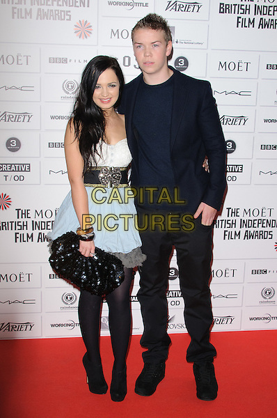 guest & Will Poulter.14th Moet British Independent Film Awards 2011, Old Billingsgate, Lower Thames Street, London, England, 4th December 2011.full length black dress suit white clutch bag blue skirt.CAP/CJ.©Chris Joseph/Capital Pictures.